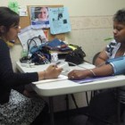 Avicenna Community Health Center/ A patient has her blood pressure and temperature checked