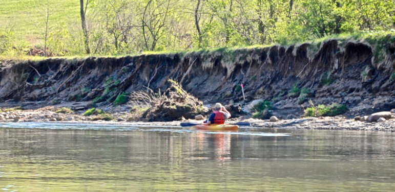 Canoeist looking at erosion on a riverbank
