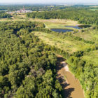 a river running next to a coal power plant and its coal ash ponds